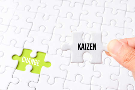 The kaizen word on white jigsaw go to replace change word on green gap - idea answer concept.