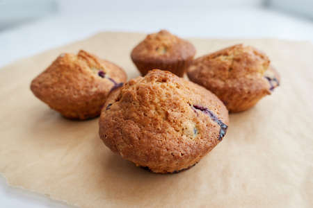 Foto für Muffins with berries on craft brown paper, close-up photo. Perfect tasty cupcakes for breakfasts, snacks, lunch or teatime. Homemade cooking and baking concept. - Lizenzfreies Bild