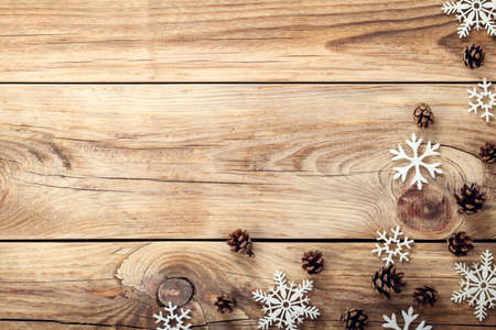 Christmas background with snowflakes and cones on wooden table with copy space