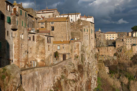 welded tuff houses in Pitigliano center, Tuscany, Italy at sunset in winter on gray sky background