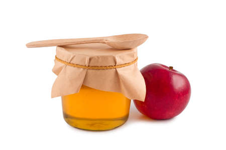 Honey in jar wooden spoon red apple isolated.の写真素材