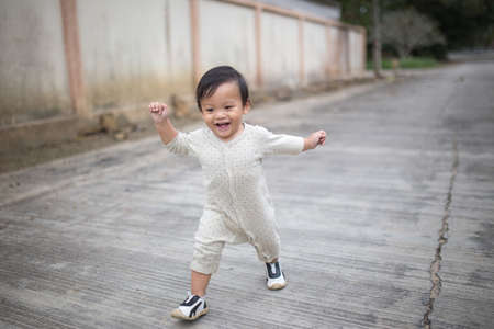 Photo pour Little baby boy walking along the street. - image libre de droit