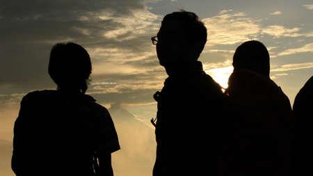 Photo pour Group of people silhouette at golden sunrise - image libre de droit