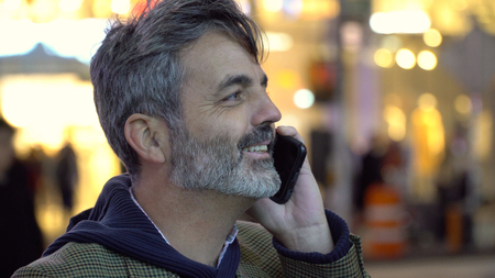 Man with beard smiling while talking on his smart cell phone call in New York City. Street people traffic walk by in background. Successful businessman professional happy urban style