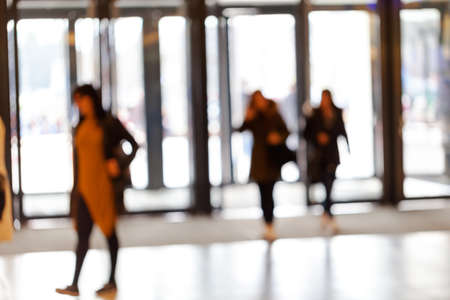 silhouettes of people as they move through the mal with light backgroundl, for the bluured background
