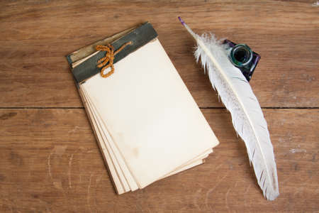 Old notebook, quill ink pen and inkwell on wood background