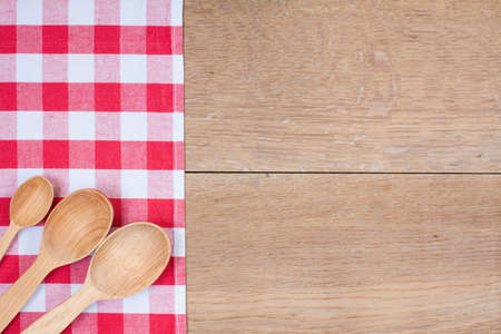 Red and white kitchen textile texture, wooden spoons on wood textured background