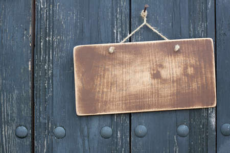 Grunge wood frame blank with rope hanging on nail on dirty planks background