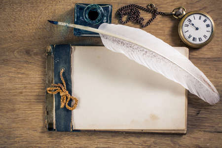 Old notebook, quill and pocket watch on wood