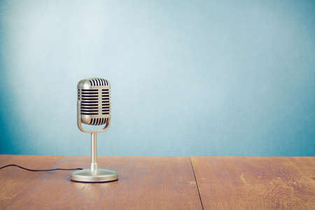 Retro style microphone on table near blue wall background