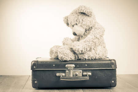 Teddy Bear toy alone on suit case retro sepia photo