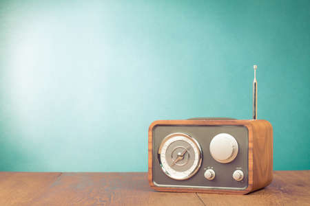 Retro style radio receiver on table in front mint green background