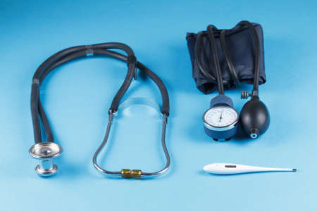 Medical devices stethoscope, tonometer, and thermometer on blue background