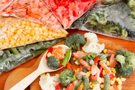 Frozen vegetables on cutting board and plastic bags