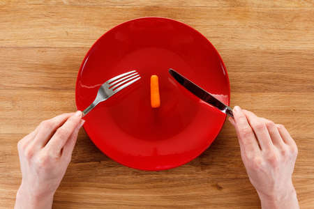 Concept of dieting, healthy eating properly. On wooden table is a plate with small carrot. Girl's hands with fork and knife, preparing to eat