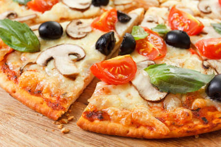 Foto de Sliced Pizza with mushrooms, olives and tomatoes. Basil, rosemary and fresh vegetables. Freshly homemade - Imagen libre de derechos