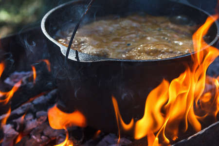 Tourist bowler with food on bonfire, cooking in the hike, outdoor activities. Preparation of pilaf or soup on fire.