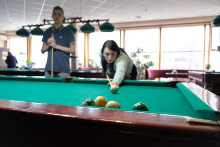 Woman playing in billiard pool hobby sport. Family sport leisure.