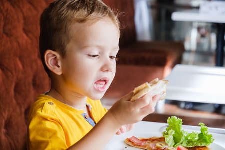 Little cute boy eating a small pizza, very eagerly