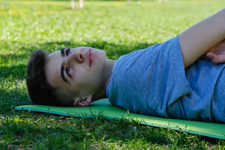 Photo for Young teen boy man lying on a grass lawn in park - Royalty Free Image