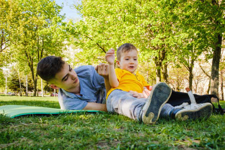 Photo pour Cheerful two brothers lie on the grass in the park and play in funny games smiling - image libre de droit
