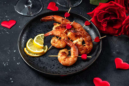 Photo pour Fried shrimp, roses and champagne on the black background. Original appetizer for Valentines Day, romantic dinner - image libre de droit