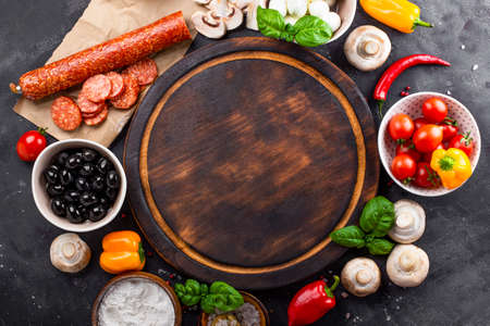 Photo for Pizza ingredients on the dark background and round cutting board, free space for text. Pepperoni, mozzarella, tomatoes, olives, mushrooms and flour are different products for making pizza and pasta - Royalty Free Image