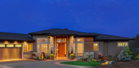 Home exterior at night: beautiful ranch style home with deep blue sky
