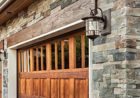 Home garage detail: garage door, sconce light, and stonework