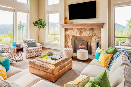 Photo pour Furnished living room in new luxury home with fireplace, ottoman, tv, couches, and colorful cushions - image libre de droit
