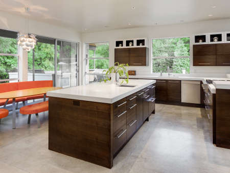 Photo pour Kitchen with Island, Sink, Cabinets and Dining Table in New Luxury Home - image libre de droit
