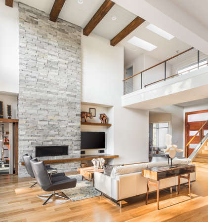 Photo pour living room interior with hardwood floors and fireplace in new luxury home with vaulted ceiling, loft area, and entrywayfoyer - image libre de droit