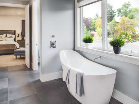 Photo pour Bathtub in master bathroom in new luxury home with view of master bedroom and neighborhood with trees  through window - image libre de droit