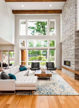 living room interior with hardwood floors, huge bank of windows, tall vaulted ceiling, and fireplace in new luxury home