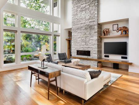 Foto de living room interior with hardwood floors, fireplace, and large bank of windows with view of lush vegetation, in new luxury home - Imagen libre de derechos