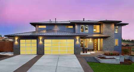 Beautiful Exterior of New Luxury Home at Sunset with Colorful Sky