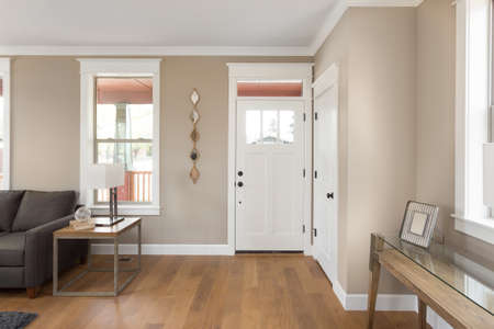 Photo pour Entryway and Foyer in New Home: Front Door with Hardwood Floors, Window and Couch - image libre de droit