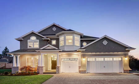 Beautiful luxury home exterior at night, with three car garage, driveway, grass yard, and covered porch