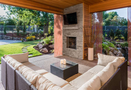 Foto de Beautiful Covered Patio with Fireplace, Television, and View of Landscaped Yard as Part of New Luxury Home - Imagen libre de derechos