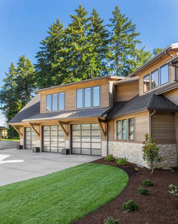 Photo pour Luxury home exterior on sunny day with blue sky. Features three car garage, large driveway, and elegant design - image libre de droit