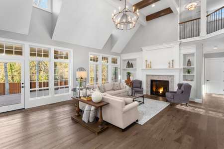 Photo pour Beautiful living room in new traditional style luxury home. Features vaulted ceilings, fireplace with roaring fire, and elegant furnishings. - image libre de droit
