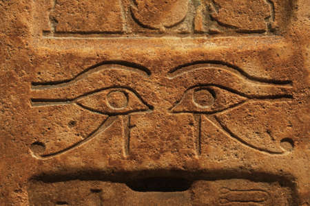 Photo pour Close up background of antique stone wall with carved ancient Egyptian bas relief of wadjet, Eye of Ra or Horus, front view - image libre de droit