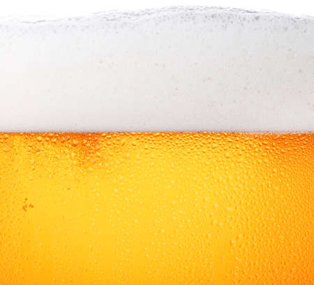 Photo pour Close up background texture of pouring lager beer with bubbles and froth in frosty glass with drops, low angle side view - image libre de droit