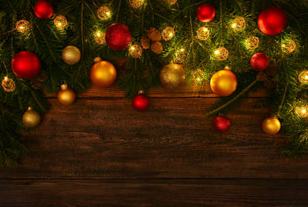 Photo pour Close up fresh green spruce or pine Christmas tree branches with cones, lights, colorful balls and baubles decoration, over dark brown wooden planks background with copy space - image libre de droit