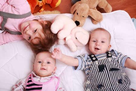 Photo pour Cute siblings with toys lying - image libre de droit