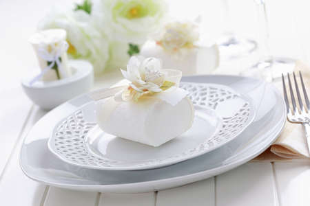 Luxury place setting in white with small present for the guests