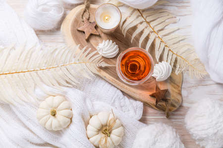 Photo pour Cosy still life for winter and autumn with glas of pink wine, pumpkin cookie, woll and warm sweater - image libre de droit