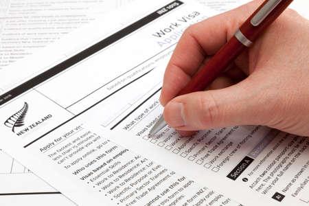 Photo pour A man holding a ballpoint pen to fill a work visa application form to New Zealand. - image libre de droit