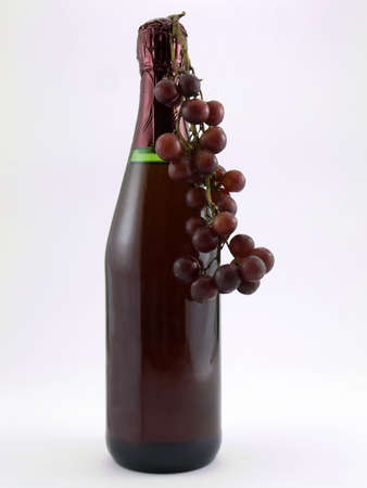 Photo of a wine bottle with red grapes hanging from it