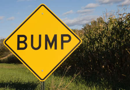 Bump road sign next to cornfield